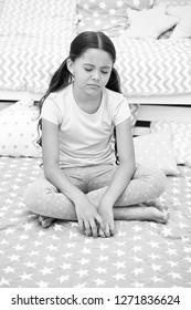 Girl child sit bed bedroom. Kid unhappy someone entered her bedroom bothering her. Girl kid long hair cute pajamas sleepy drowsy unhappy face. Let her sleep longer. Lack of sleep schoolgirl regime.