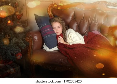 girl child sleeps on the couch, covering himself with a plaid at the Christmas tree