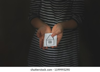 A girl is a child with a small house in her hands, the concept of a dream about her own home