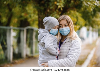 a girl with a child stands on the road in a protective medical mask. Dense smog on the streets. Epidemic of the flu