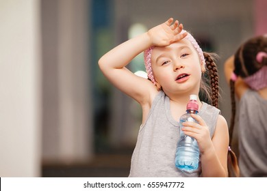 Girl child is tired after training fitness exercises in health club, drink water, stretching in exercise, workout, wearing sportswear, indoor full length, pink color. Keeping our bodies fit.