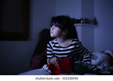 girl child watching tv in bed at night
