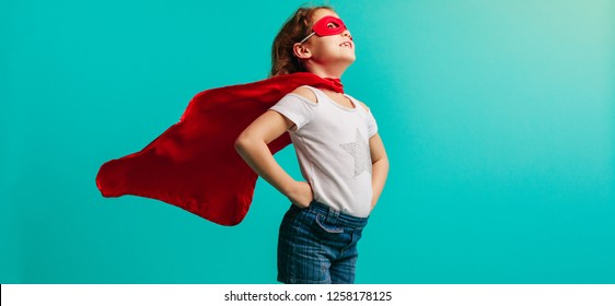 Girl child wearing red  costume standing with her hands on hips in studio. Girl in red cape and mask looking away on blue background.