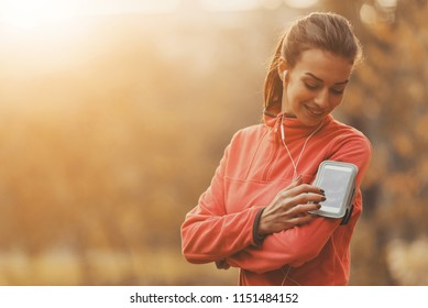 Girl Choose Music for Running. In Autumn Park. Young Beautiful Woman Doing Sports. Listening Music Composition. Fmale With Headphones. Fitness Concept. Running in Park. Sport Lifestyle.