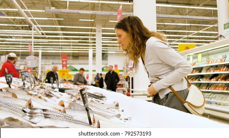 Girl chooses a fish in a fish department in a supermarket, 4k.