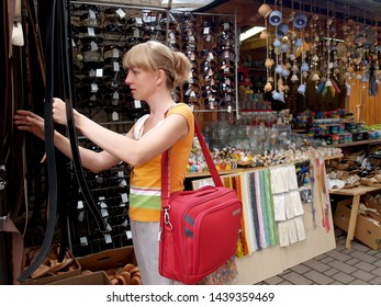 The girl chooses a leather belt in a haberdashery bench