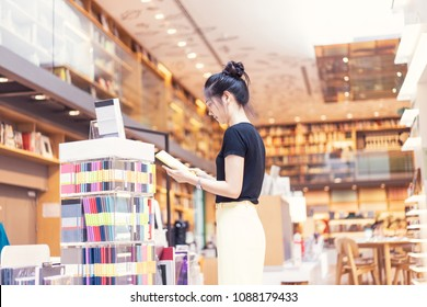 A girl is choosing a book and notebook at the bookstore in department store.