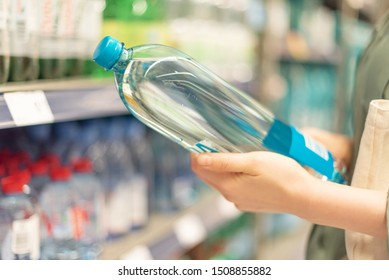 Girl choosing bottle of drinking water in grocery section of supermarket. Copy space. Water balance and body hydration. Healthy diet concept. Sustainable lifestyle
