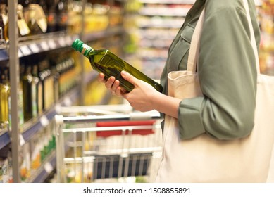 Girl choosing bottle of oil in grocery section of supermarket. Copy space. Healthy diet concept. Sustainable lifestyle