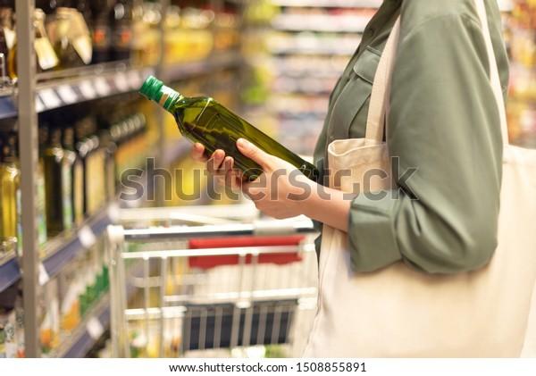 Fille choisissant une bouteille d'huile dans la section épicerie du supermarché. Copier l'espace. Concept de régime sain. Mode de vie durable
