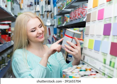 Girl choosing decorating paint in household section of supermarket
