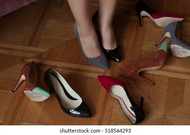 Girl choosing a pair of high heels shoes. Sitting on pink velvet elegant sofa. Hard choice.  Beautiful legs. Shopping at store. Choosing perfect pair