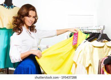Girl choosing yellow skirt during sale in shop