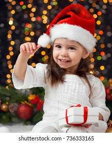 girl in christmas decoration with gift, dark background with illumination and boke lights, winter holiday concept