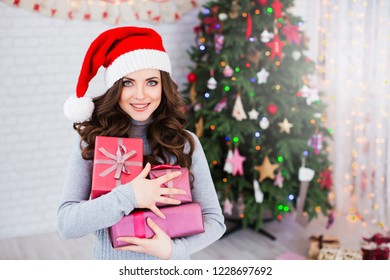 Girl in Christmas. Happy cheerful woman celebrating new year with gifts near Christmas tree.