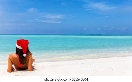 Girl with Christmas hat and bikini lying on tropical beach