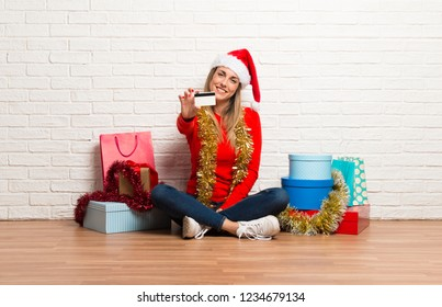 Girl with christmas hat and many gifts celebrating the christmas holidays holding a credit card