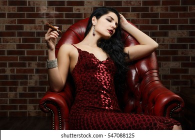 Girl with a cigar in a dark room. Red dress. fumes of cigars