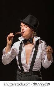 The girl with cigar in men's suit and tie butterfly, against dark background. (rigid light and shadows)