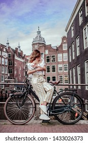 Girl in the city of Amsterdam looks into the distance. Concept bike trip.