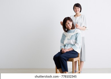 A girl clapping her mother's shoulder