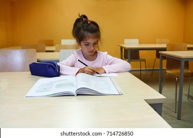 A girl is in the class and learning to read and to write with a pencil, she is writing with a pen in her notebook