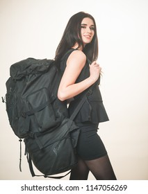 Girl classic black dress and touristic backpack equipment. Business lady travelling with backpack. Woman carry baggage on her back. Woman takes with her all she owns. Elegance and capaciousness