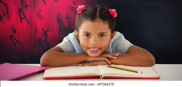 Girl clenching teeth while leaning on book against black background