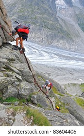 girl climber on a rock face ladder, climbing down with glacier in the background and no security