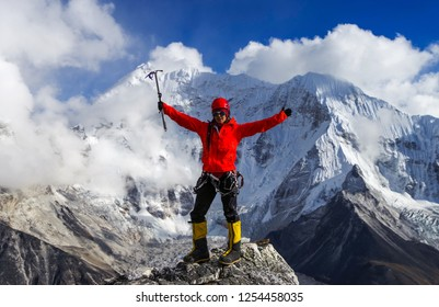 Girl climber raises hands on the background of Himalayas, Everest region, Nepal