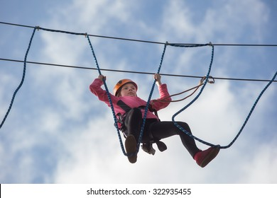 girl climbing in adventure rope park