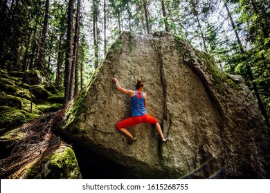 girl climbing hard boulder problem in forest. Sport climbing, bouldering.