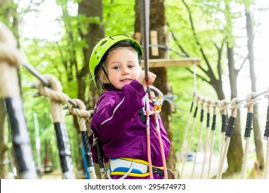 Girl climbing in high rope course enjoying the adventure