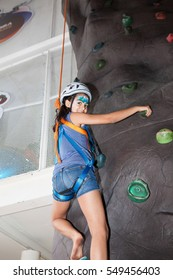 Girl climbing indoor using rope and helmet
