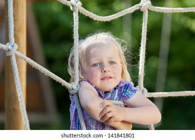 Girl is climbing a net at playground