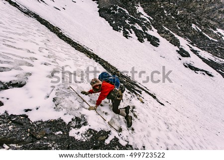 A girl climbing on a steep slope through the stones and ice in Himalaya mountains. Nepal.