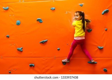 Girl climbing on a wall in attraction playground