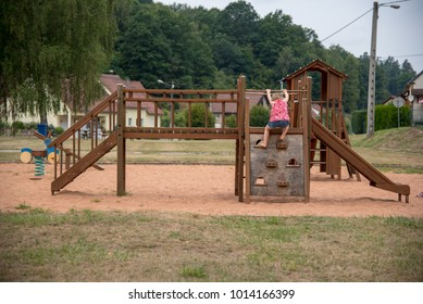 Girl climbing on wooden public games, France.
