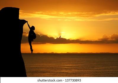 Girl climbing a tall mountain at sunset