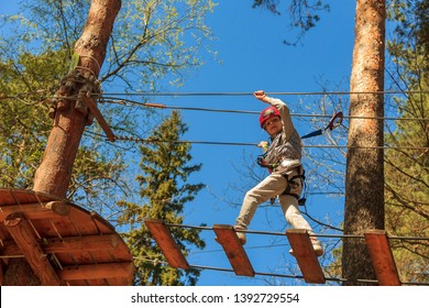 Girl climbs adventure park. Adorable little girl enjoying her time in climbing adventure park on warm and sunny summer day. Summer activities for young kids. Child having fun on school vacations.