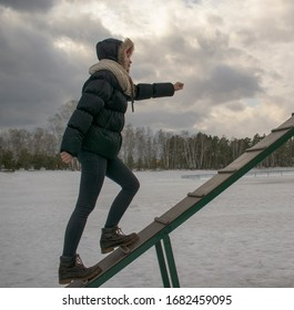 Girl climbs up the inclined board. Profile view. Holds a hand forward. Black jeans and a jacket with a hood. Winter, snow, trees, sky with clouds. Leadership concept, personal growth, career.