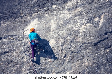 The girl climbs the rock. The climber in helmet trains on a natural relief. Extreme sport. Active recreation in nature. A woman overcomes a difficult climbing route.