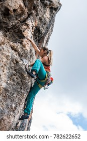 Girl climbs rock tufa