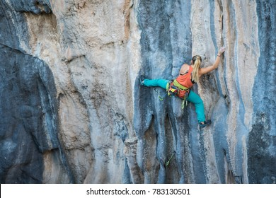 Girl climbs rock tufa