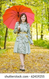 girl in cloak with umbrella in autumn park