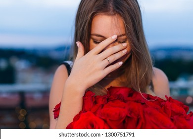 the girl closed her face with her hand and ring on her ring finger. she holds a bunch of roses