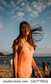 girl with a closed pink swimsuit on the beach sunset