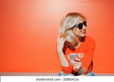 girl close-up of a beautiful young blonde in the street lifestyle  hipster on a red background with red lips smiling in sunglasses with her hands with a red manicure with a telephone selfie hipster