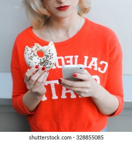 girl close-up of a beautiful young blonde in the street lifestyle on  background with red lips smiling in sunglasses  with a red manicure jeans with a telephone selfie hipster eating a donut