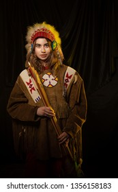 The girl in clothes and a headdress of native americans in yellow light against a dark background
